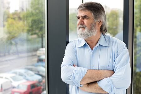 gray beard: old men in blue shirt and gray beard standing next to a big window thinking at something Stock Photo