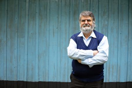 bejaarde man stond buiten op blauwe houten achtergrond Stockfoto