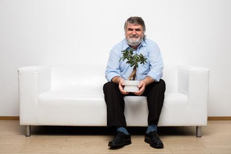 tending: single old men sitting on white couch, tending a bonsai