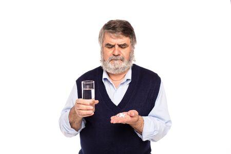tomando refresco: anciano con barba gris con un vaso de agua y pastillas en las manos, aislado en blanco