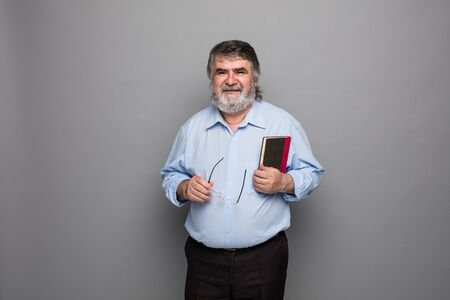 real leader: old professor with gray beard standing with a book in hand