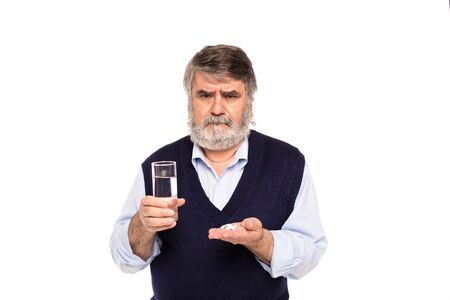 tomando refresco: old man with gray beard having a glass of water and pills in hands, isolated on white