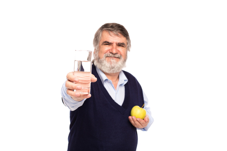 gray beard: old man with gray beard having a glass of water and green apple in hands, isolated on white Stock Photo