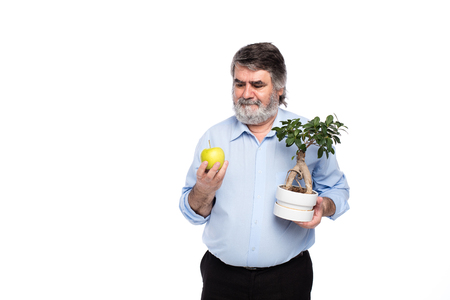 earth handful: old men with gray beard holding a small tree and green apple in in hands, isolated on white
