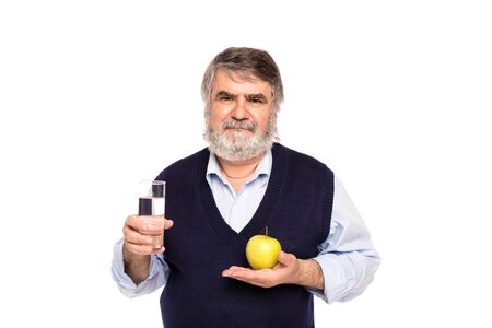 white beard: old man with gray beard having a glass of water and green apple in hands, isolated on white Stock Photo