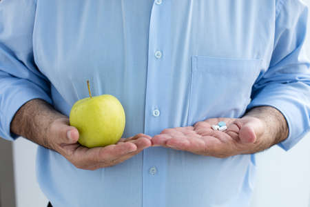 hand holding pills: old men holding some pills in one hand and green apple in other hand