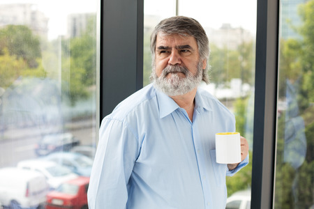 gray beard: old teacher with gray beard and blue shirt drinking coffee next to a window