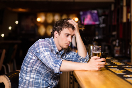 sad single man drinking beer at bar or pub, using his cellphone, texting or betting