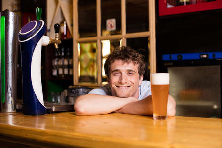 bartending: young bartender serving beer in a pub