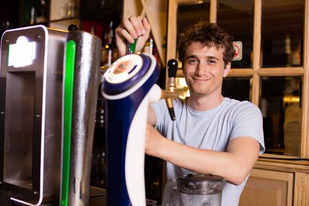 bartending: young bartender serving beer in a pub