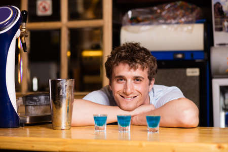 bartending: young bartender preparing blue coktail in a pub