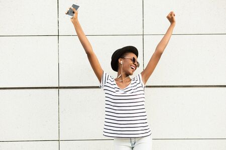 african dance: happy modern young black woman with sunglasses, hat and striped shirt  listening music outside and dancing