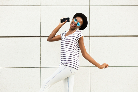 mujer joven negro moderna feliz con gafas de sol, sombrero y camisa de rayas de música escucha fuera y baile