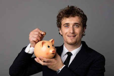 introducing: handsome elegant man introducing a coin in a piggybank on gray background