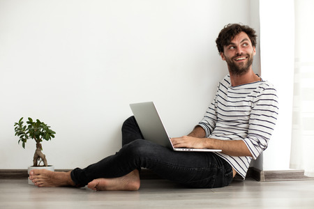young man with stripped blouse sitting down on the floor looking for a job at leptop with a plant next to him Standard-Bild