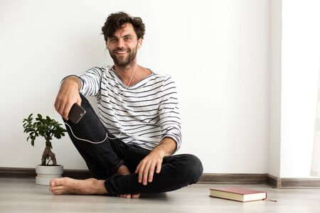 young man in stripped blouse listening music at his mobile and sitting down on the floor next to a book and a plant