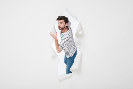 casual man in stripes and jeans breaking the paper wall Stock Photo