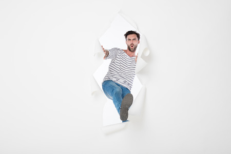 casual man in stripes and jeans breaking the paper wall, pasing from side to side Stock Photo