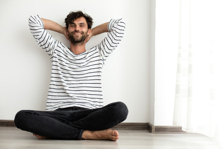 relaxed man sitting happy on the floor next to a window with natural light Banque d'images