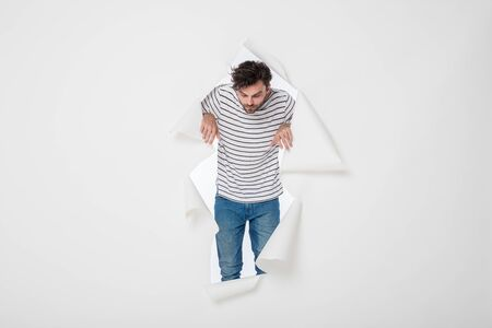 casual man in stripes and jeans breaking the paper wall, looking to one side