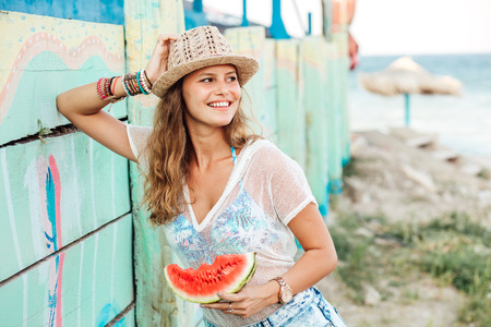 beautiful young woman having a slice of watermelon in hands, standing and smiling on a colored wall somewhere in vacation