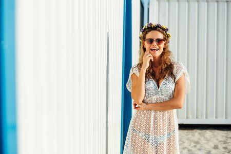 young cute girl, wearing a wreath of flowers, standing in sunlight with sunglasses next to a white wall somewhere on the beach, woman of summer concept