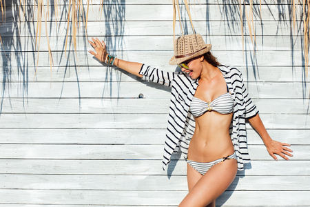 young woman wearing hat, sunglasses and bathing suit marine style, standing on wooden vintage wall with reed in full sunlight