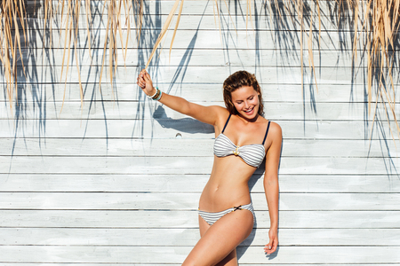 young sexy woman wearing  marine swimsuit, playing with reeds hanging on a wooden wall in full sunlight