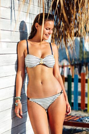 personas banandose: mujer sexy joven con traje de baño marino, disfrutando de la luz del sol en una pared de la vendimia de madera blanca con la caña que pesa sobre Foto de archivo
