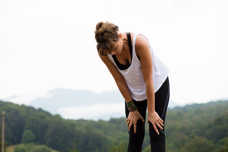 young athletic woman stretching and preparing to do sport somewhere in nature on top of the mountains