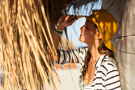beautiful woman wearing a summer hat and a marine shirt, standing under a thatched roof that makes nice shodows on her face near a wooden wall Stock Photo