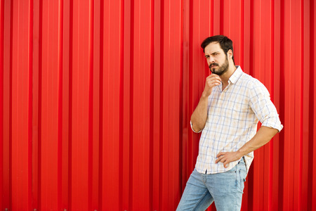 free thinking: adult masculine man in casual outfit thinking about something turned in one side with free open space on a red industrial wall