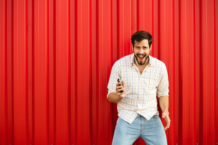 verry: excited adult man with cellphone and headsets smiling verry happy and dancing on red background outside in natural light