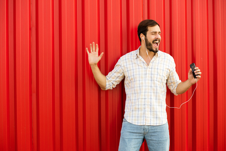 very happy man with cellphone and headsets on red background Stock Photo
