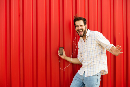 handsfree telephone: excited adult man with cellphone and headsets smiling verry happy and dancing on red background outside in natural light