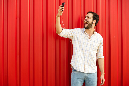 handsfree telephone: happy man smiling at his cellphone on red background with free space