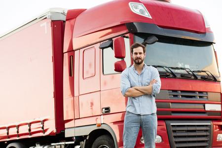 apuesto conductor del camión masculina de pie fuera con su vehículo detrás con los brazos cruzados Foto de archivo