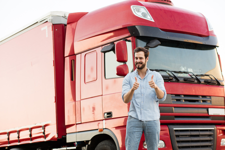 handsome masculine truck driver standing outside with his vehicle behind with pointing the camera Standard-Bild