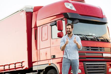 knappe mannelijke vrachtwagenchauffeur permanent buiten met zijn voertuig achter met de camera te wijzen Stockfoto