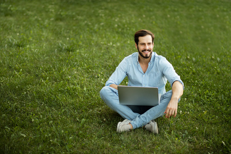 comunication: smiling man with laptop in hands lying down in grass outside