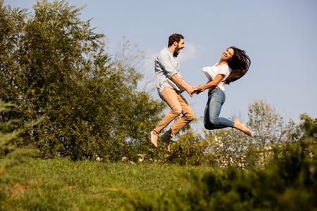 jonge gelukkige paar springen met geluk als gevolg van een goed nieuws, ergens buiten in de natuur