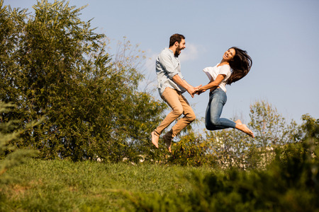 joven pareja feliz saltando de alegría a causa de una buena noticia, en algún lugar fuera de la naturaleza