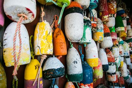 Flotadores de langosta coloridos que cuelgan en una tablilla resistida de la langosta del hombre de la cabaña en un trabajo