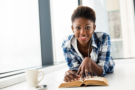 smiling young black woman, listening music from her cellphone, lying on the floor and relaxing next to a window with a book in front and a cup of coffee, looking to camera Stock Photo - 69913611
