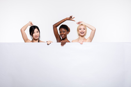 concept with three different ethnicity women, asian, afro american and caucasian, over a white empty panel with free space smiling and looking naked isolated Stock Photo