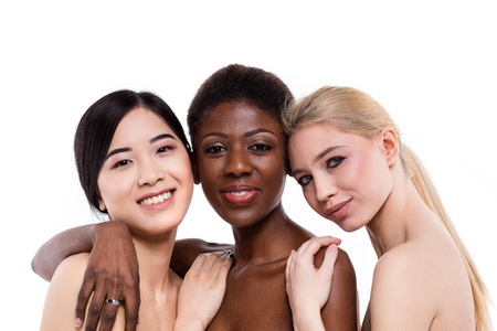 concept of three different ethnicity of women being very close one to each other and looking naked and expressing friendship on white background