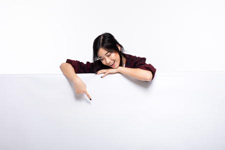 smiling cute asian young woman pointing an empty white board casual dressed, isolated on white