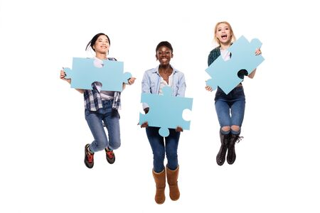 pices: happy three different women, asian, caucasian and afro amerian, jumping with joy showing puzzle pices on white background Stock Photo
