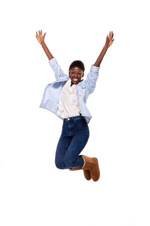 afro amerian woman jumping and smiling on white background