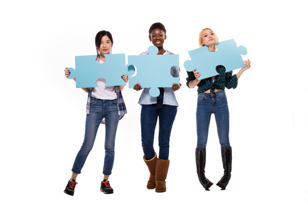 pices: happy three different women, asian, caucasian and afro amerian, showing puzzle pices on white background